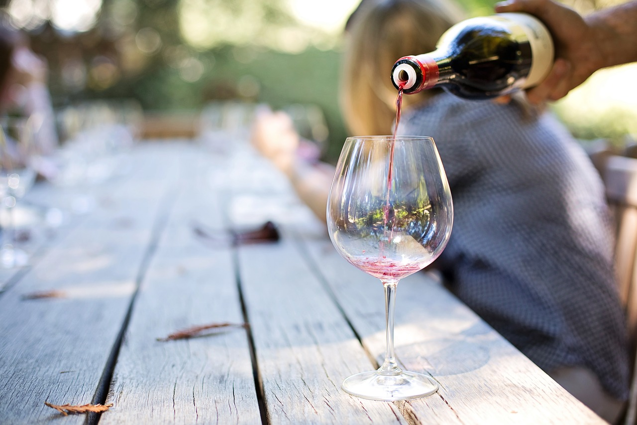 Wine Tasting 101: picture of a glass of wine being poured outside on a wood table